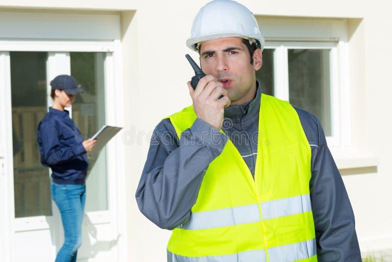 Capo mastro di costruzione che d? ordine tramite il walkie-talkie immagine stock