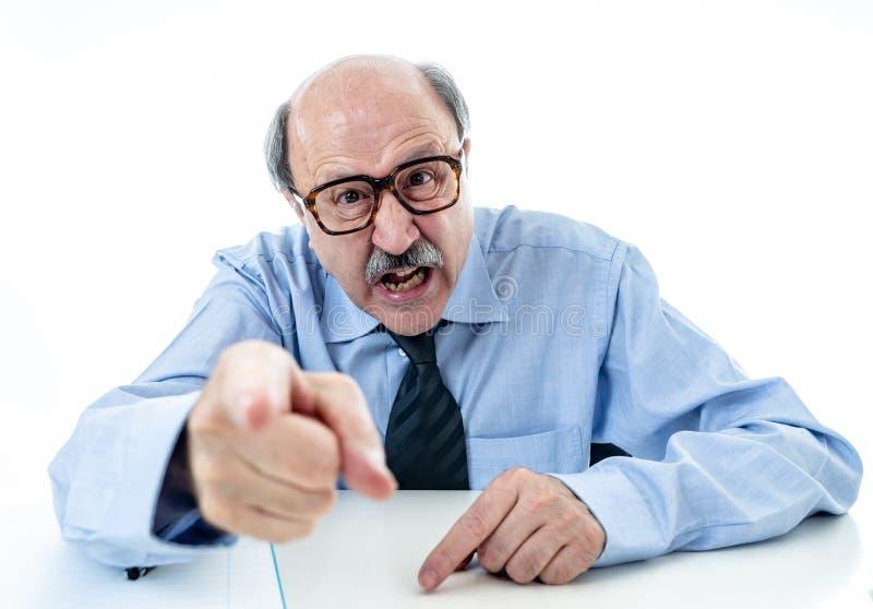 Capo più anziano arrabbiato sul lavoro che urla e che discute all'ufficio fotografia stock