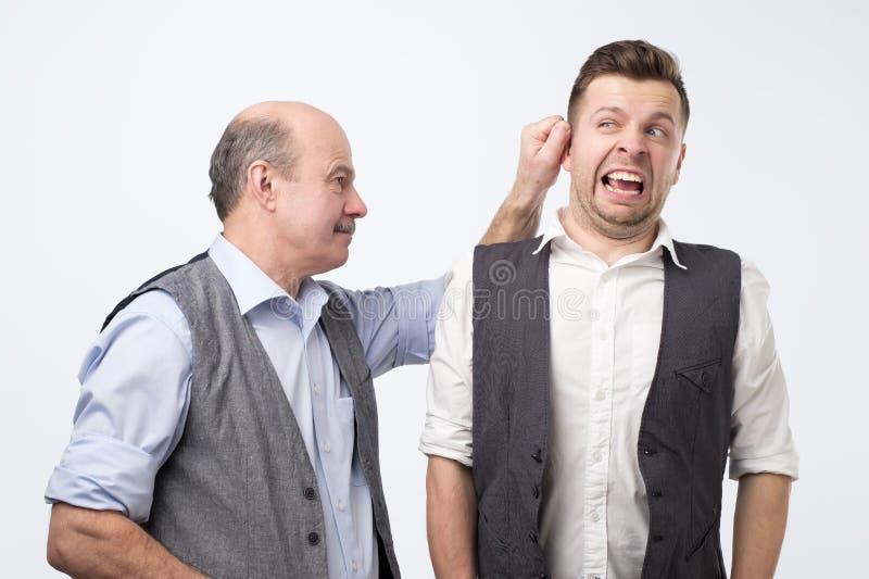 Capo senior che tira l'orecchio del giovane, punente per l'errore sul lavoro fotografie stock
