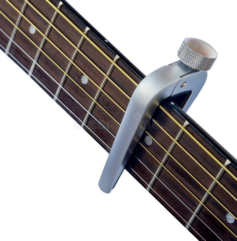Capo sur la touche de guitare, fond blanc images libres de droits