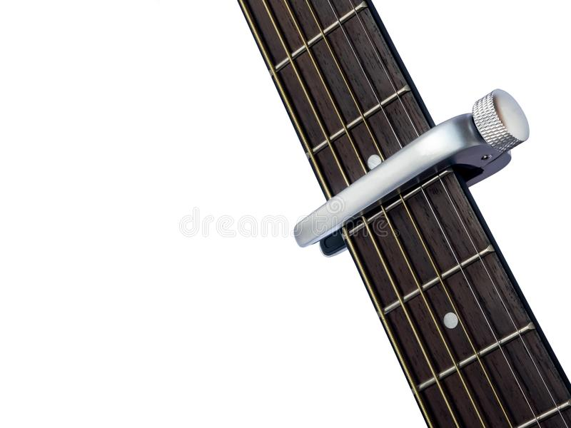 Capo sur la touche de guitare, fond blanc photo stock