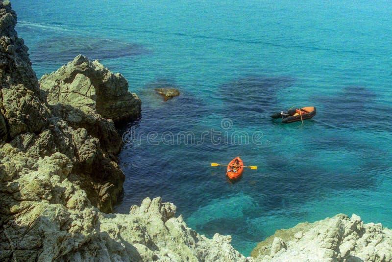 CAPO VATICANO, ITÁLIA, 1985 - mãe e filho em um enfileiramento de borracha da canoa entre as rochas no mar esplêndido do Capo  fotografia de stock royalty free