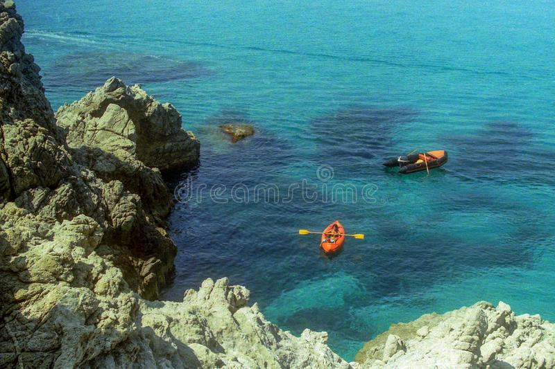 CAPO VATICANO, ITALY, 1985 - Mother and son in a rubber canoe rowing between the rocks in the splendid sea of Capo Vaticano.  royalty free stock photography
