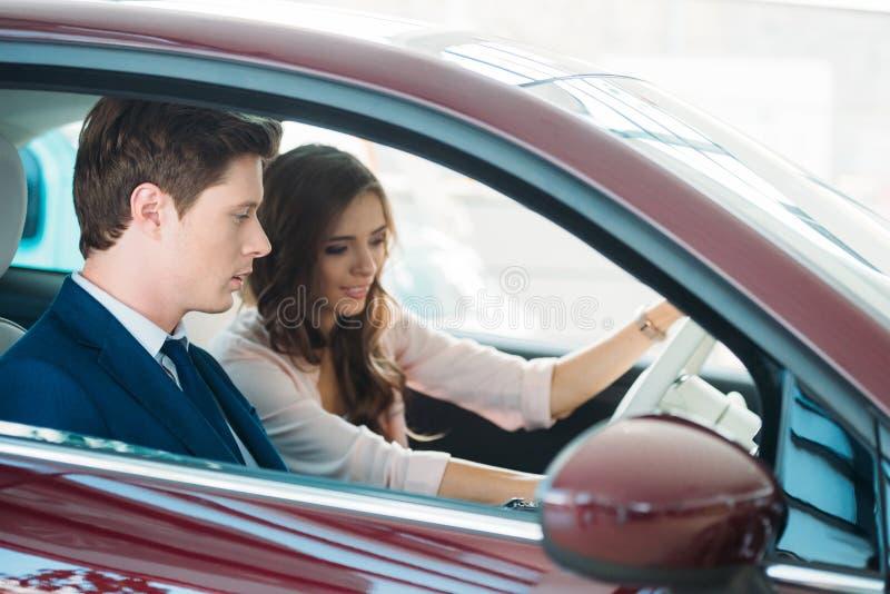 Capo vendite che si siede in una nuova automobile con un bello cliente fotografie stock