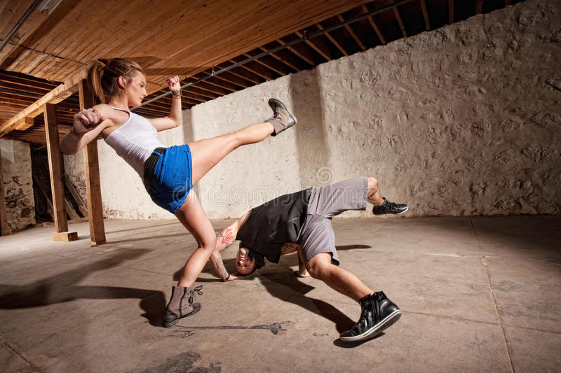 Capoeria Experts Kicking and Dodging. Male and female capoeria sparring partners working out stock image
