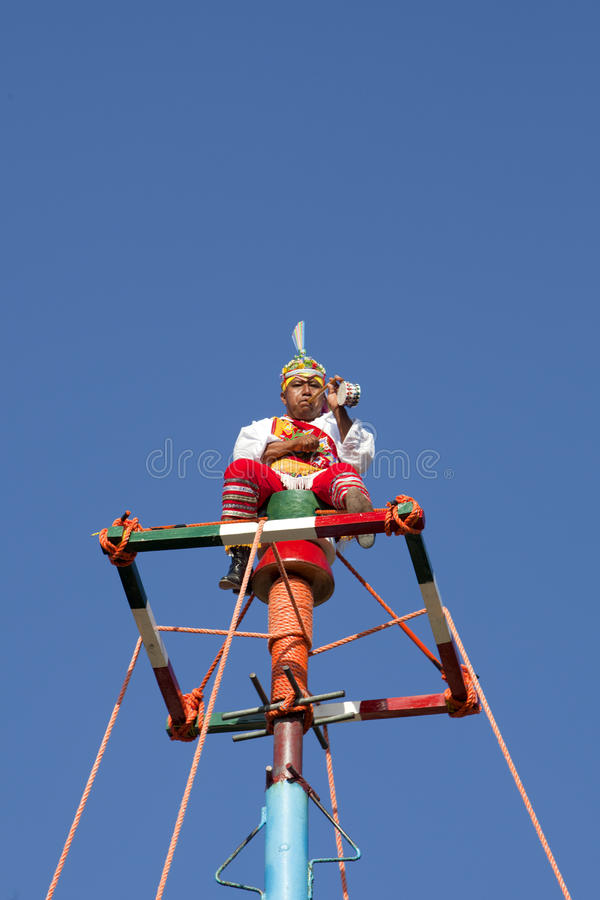 The Caporal of the Voladores. The caporal plays a drum and flute a top the pole. The voladores, or flyers, of Tulum dress in brilliantly colored traditional royalty free stock image
