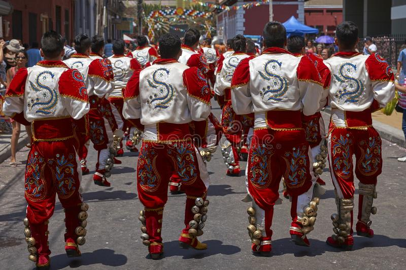 Caporales dancers at the carnival in Arica, Chile. Caporales dancer in ornate red and white costume performing at the annual Carnaval Andino con la Fuerza del stock photo