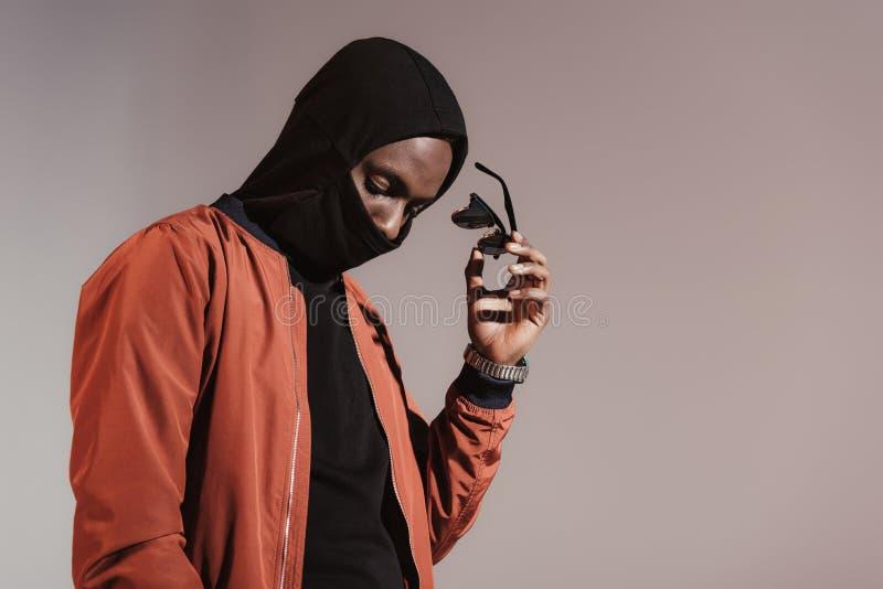 Capot de port de jeune homme élégant d'afro-américain avec le masque protecteur et la prise de ses lunettes de soleil image libre de droits