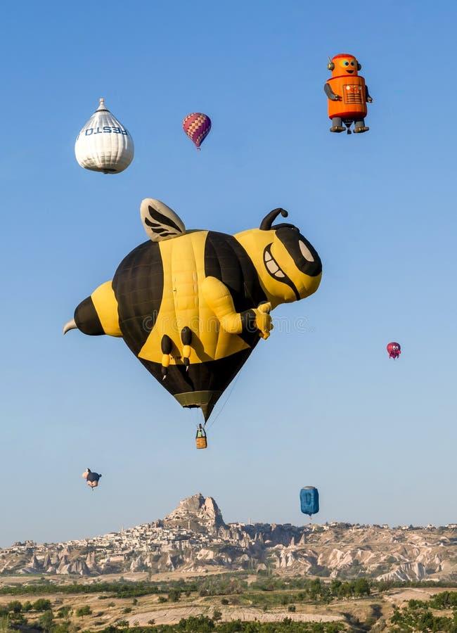 Cappadocia/die Türkei - 7. Juli 2019: Verschiedene Karikaturformballone um Uchisar-Region während des Cappadocia-Ballon-Festivals stockbild