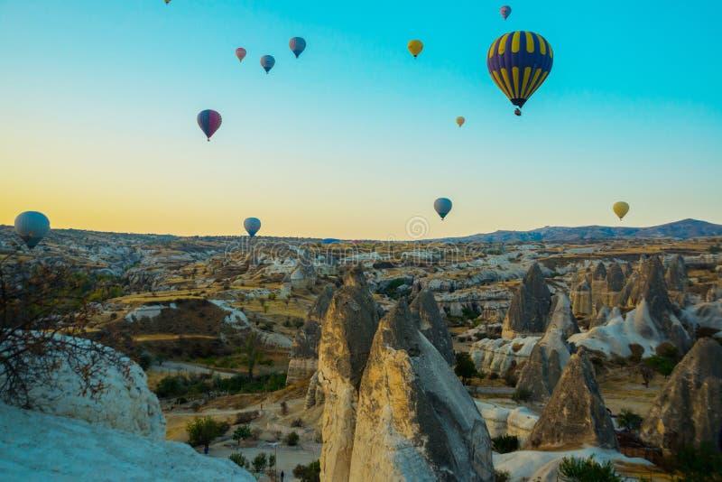 Cappadocia, Goreme, Анатолия, Турция: Красочные горячие воздушные шары летая над ландшафтом утеса, Cappadocia знаны по всему миру стоковое изображение