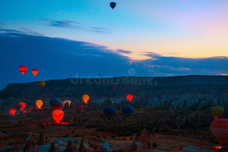 Cappadocia, Goreme, l'Anatolia, Turchia Le mongolfiere che sorvolano le montagne abbelliscono il tramonto Cappadocia immagini stock libere da diritti