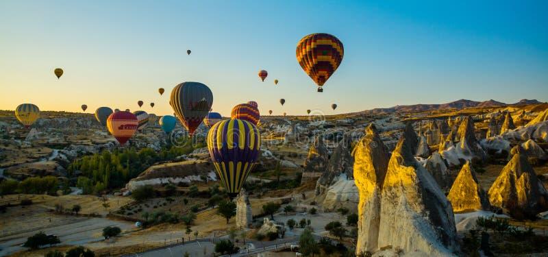 Cappadocia, Goreme, l'Anatolia, Turchia: Vista vibrante scenica del volo dei palloni in valle di Cappadocia nei raggi di alba immagini stock