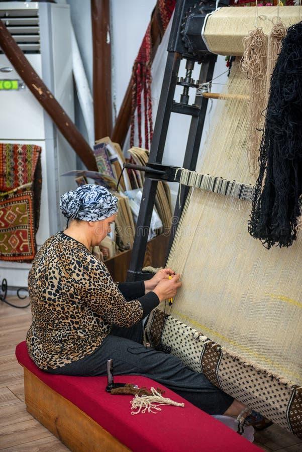 CAPPADOCIA - MAJ 17: Kvinna som arbetar på tillverkningen av matta arkivfoton