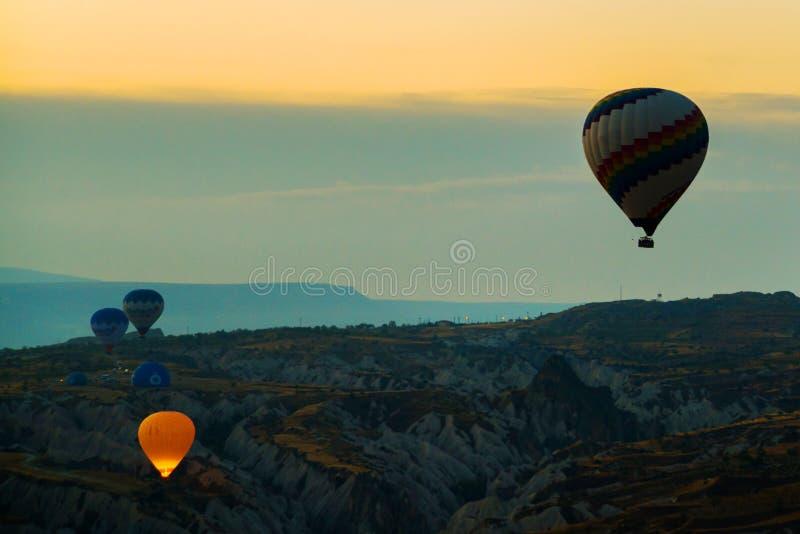 Cappadocia, Turchia: Cappadocia ad alba - paesaggio con le mongolfiere che sorvolano la valle della montagna al sole e foschia fotografia stock libera da diritti