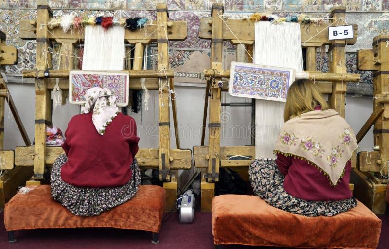 Cappadocia / Turkey - April, 26, 2013: Women weaves carpet used silkworms for carpets manifacture in Turkey. Cappadocia / Turkey - April, 26, 2013: Women weaves royalty free stock photo