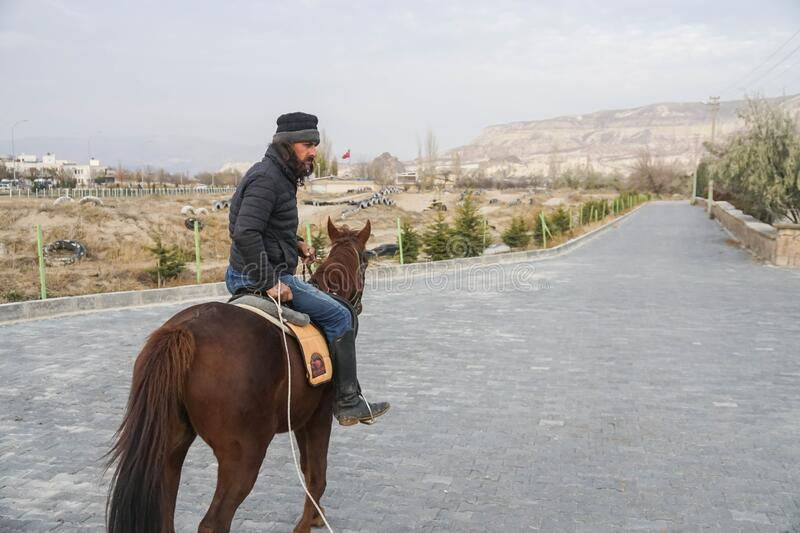 Cappadocia / Turkey - December 7 2019: cool man with middle age on horse back walking on the street town to Rose Valley. In the morning stock photography