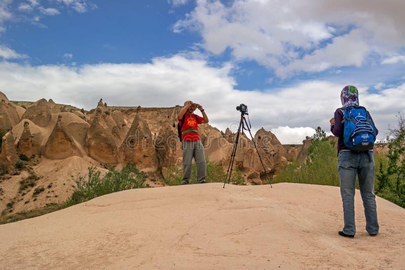 Cappadocia Turkiet - April 29, 2014: Röd dal för stenkolonner Turister fotograferas på en bakgrund av geologiska bildande royaltyfria bilder