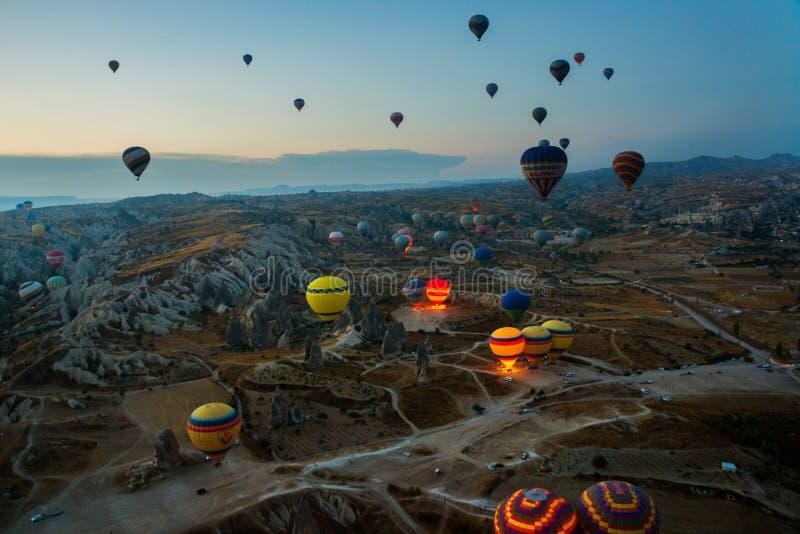 Cappadocia Turkiet: Ballonger för varm luft flyger under soluppgång i den Cappadocia regionen av Turkiet royaltyfri bild