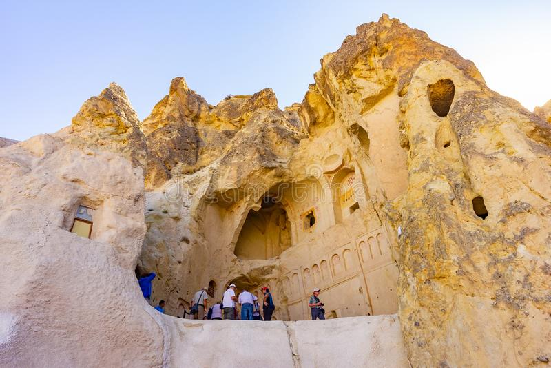 Cappadocia Turkiet, September 13, 2018: Turister som ser den forntida kyrkan, den största vagga-snitt kloster av fotografering för bildbyråer