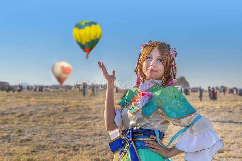 Cappadocia/Turkije-Juli 07 2019: Vrouw in kleurrijke kleding in ballonfestival en ballons en mensen op achtergrond royalty-vrije stock foto's