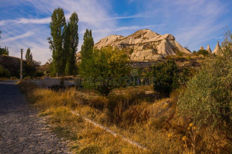 Cappadocia, Turquia: A estrada que conduz às casas e às igrejas da rocha no parque nacional de Goreme Chaminé feericamente em um  fotografia de stock royalty free