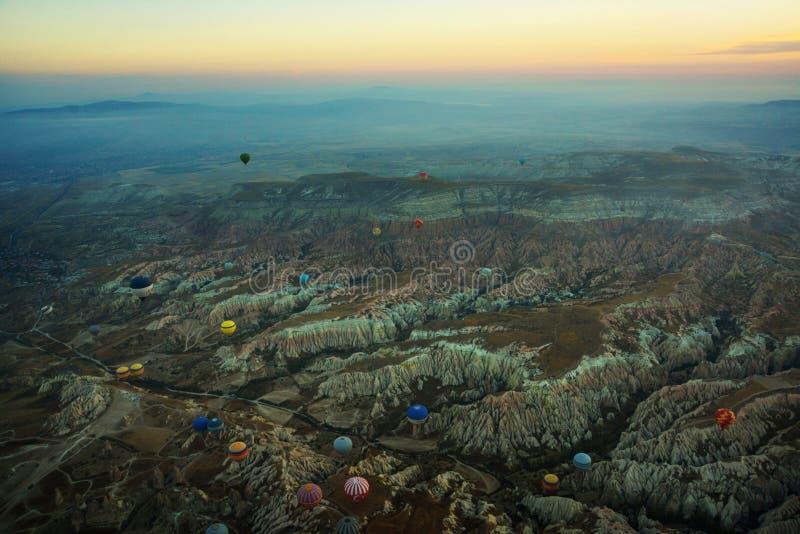 Cappadocia, Turquia: Vista superior cedo na manhã do balão, da paisagem enevoada com névoa com montanhas e dos balões coloridos fotos de stock royalty free
