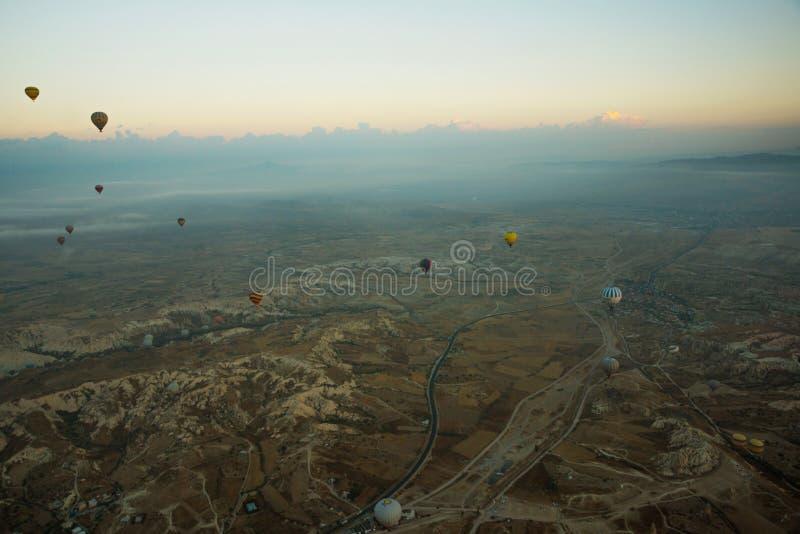 Cappadocia, Turquia: Vista superior cedo na manhã do balão, da paisagem enevoada com névoa com montanhas e dos balões coloridos imagens de stock royalty free
