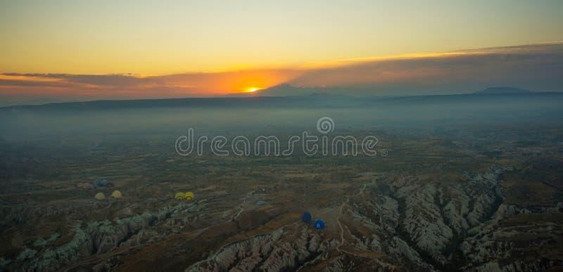 Cappadocia, Turquia: Vista superior cedo na manhã do balão, paisagem enevoada com névoa com montanhas foto de stock