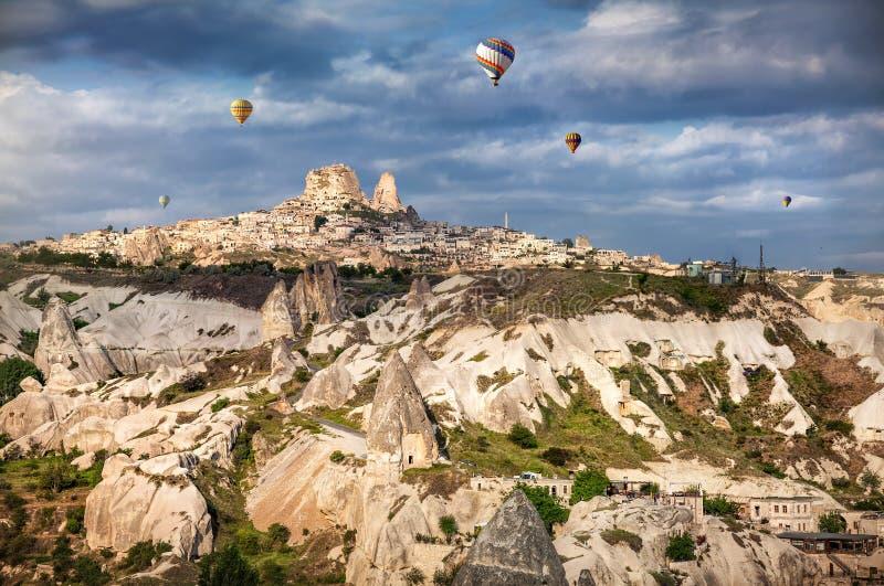 Cappadocia Uchisar castle and hot air balloons stock photos