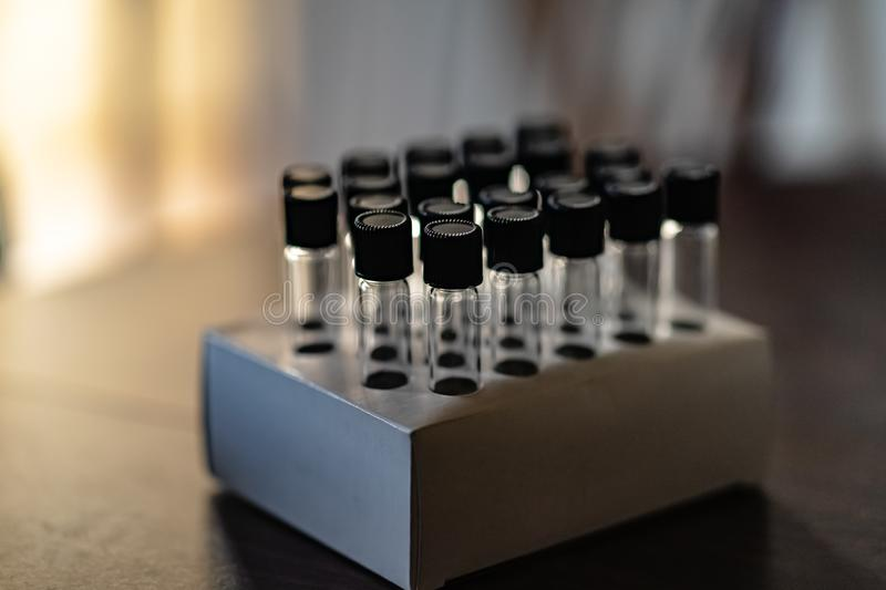 Capped and sealed glass test tubes in a rack in a lab or business ready for use stock image