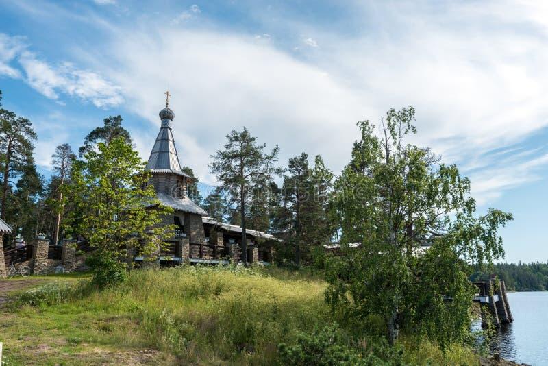 Cappella in nome di tutti i san di Valaam sulla costa dell'isola circondata dai bei alberi ed arbusti fotografia stock libera da diritti