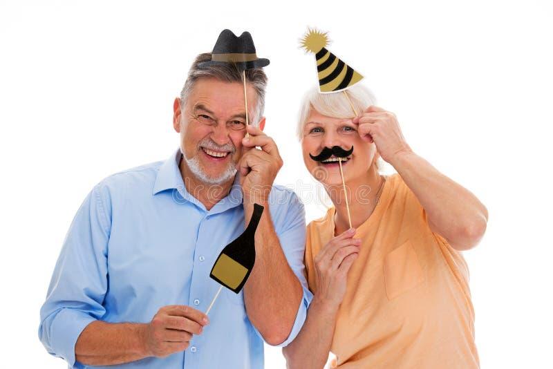 Cappelli e baffi senior divertenti del partito della tenuta delle coppie sui bastoni fotografia stock libera da diritti