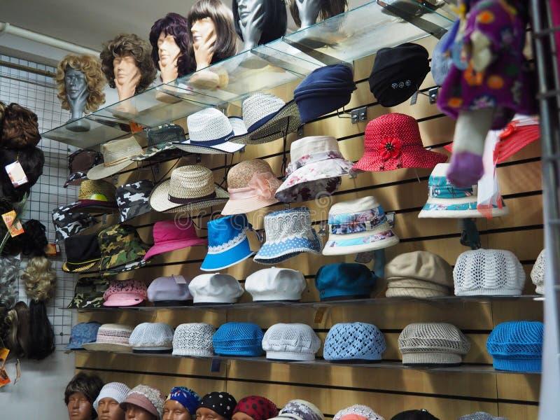 Cappelli sugli scaffali e manichini in parrucche nel deposito fotografia stock