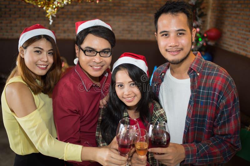Cappello asiatico del Babbo Natale di usura di donna e dell'uomo e vetro del champagne della tenuta a disposizione nella festa di immagine stock libera da diritti