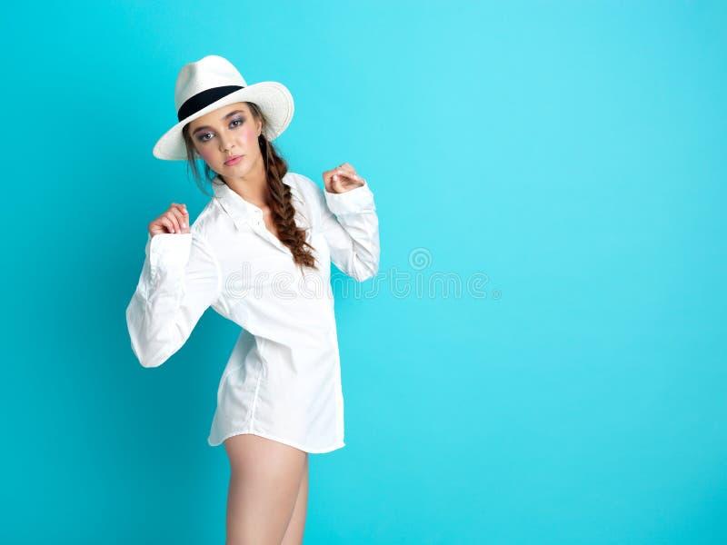 Cappello bianco della priorità bassa blu della giovane donna, camicia fotografie stock