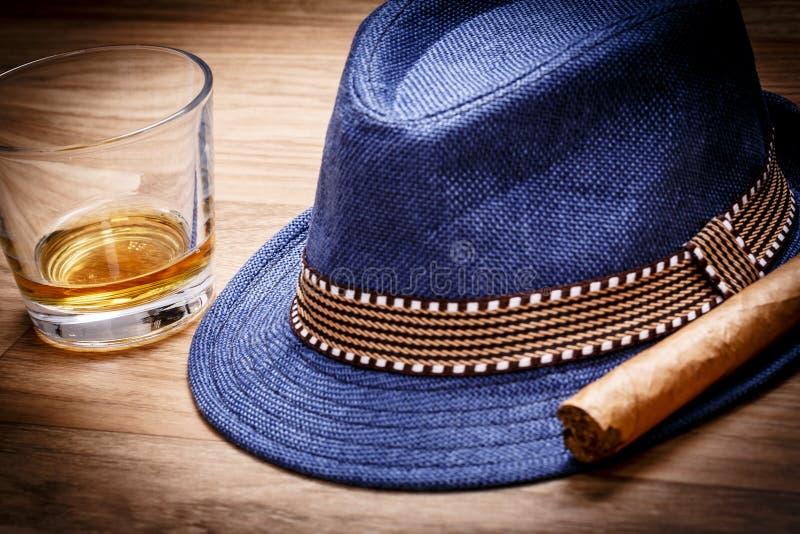 Cappello blu con il sigaro e la bevanda costosa di whiskey o di rum sul pavimento di legno fotografia stock