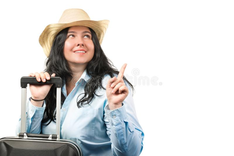 Cappello d'uso della bella giovane donna castana con la valigia isolata su fondo bianco Copi lo spazio Concetto di turismo immagine stock