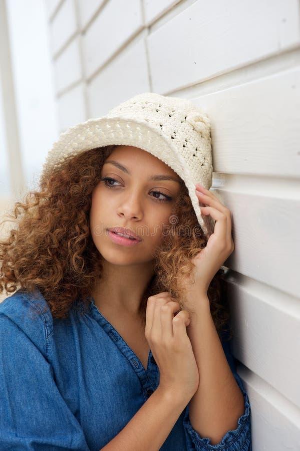 Cappello d'uso della giovane donna bella e pendere contro la parete immagini stock libere da diritti