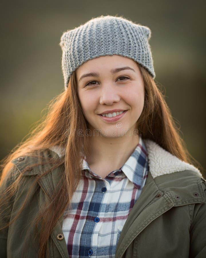 Cappello d'uso della ragazza teenager e sorridere in camera immagine stock