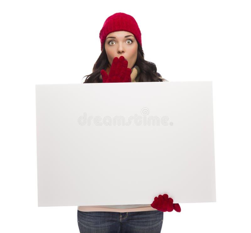 Cappello d'uso di inverno della ragazza sgomento e segno in bianco delle tenute dei guanti fotografia stock