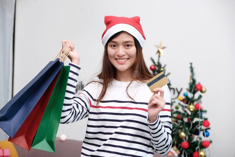 Cappello d'uso di Natale della giovane donna sveglia dell'Asia ed acquisto di tenuta fotografie stock libere da diritti