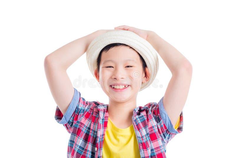 Cappello d'uso e sorrisi del giovane ragazzo sopra bianco immagine stock