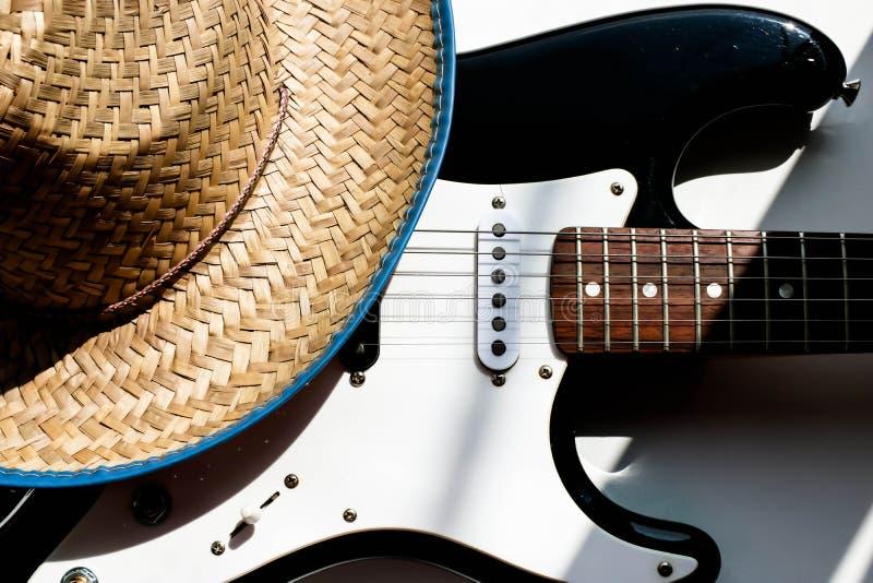 Cappello da cowboy sulla chitarra elettronica Priorit? bassa bianca Concetto o fondo di musica country Coltura americana fotografia stock
