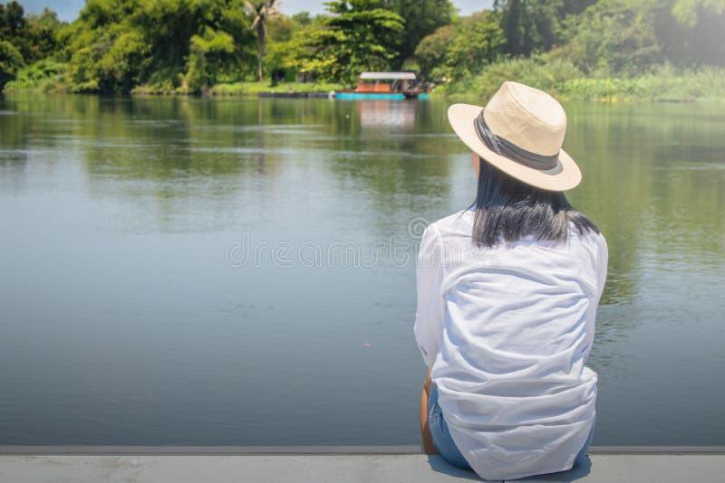 Cappello da solo asiatico del tessuto di usura di donna e camicia bianca con la seduta sul terrazzo di legno fotografia stock