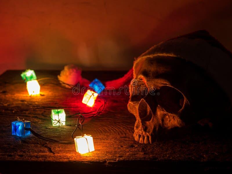 Cappello del Babbo Natale di usura del cranio di natura morta con il lampeggiatore del regalo fotografia stock