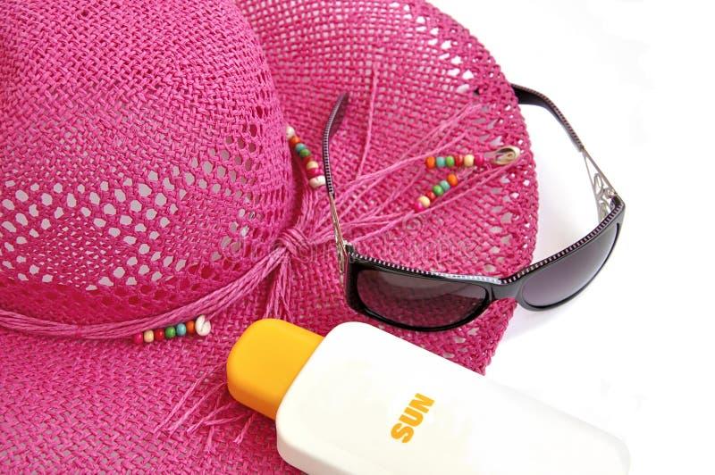 Cappello della spiaggia, bottiglia di balsamo solare. fotografia stock