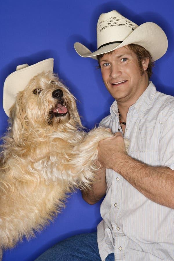 Cappello di cowboy da portare dell'uomo e del cane immagini stock libere da diritti