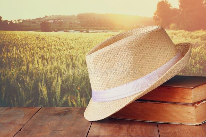 Cappello di Fedora e pila di libri sopra la tavola di legno e campo del fondo del lato del paese del grano concetto di vacanza o  fotografia stock libera da diritti