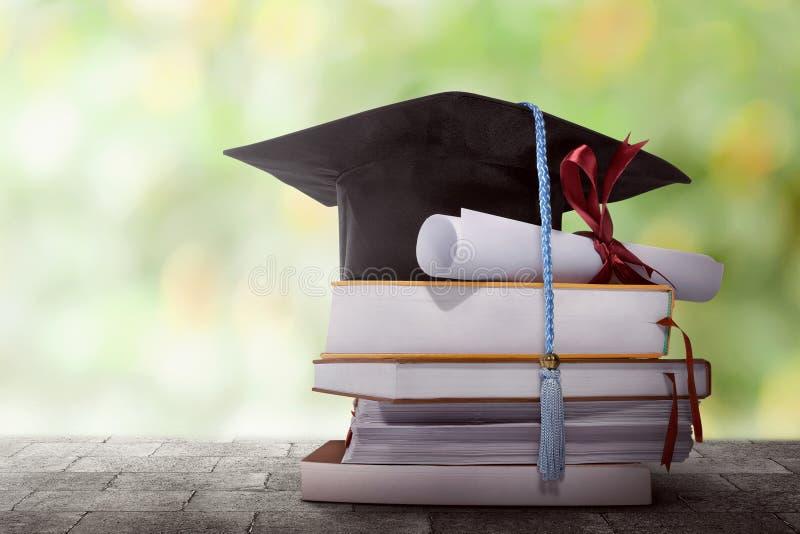 Cappello di graduazione con la carta di grado su una pila di libro immagini stock libere da diritti