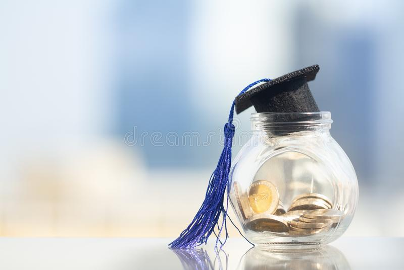 Cappello di graduazione con la nappa blu sopra il barattolo o il porcellino salvadanaio di vetro fotografia stock libera da diritti